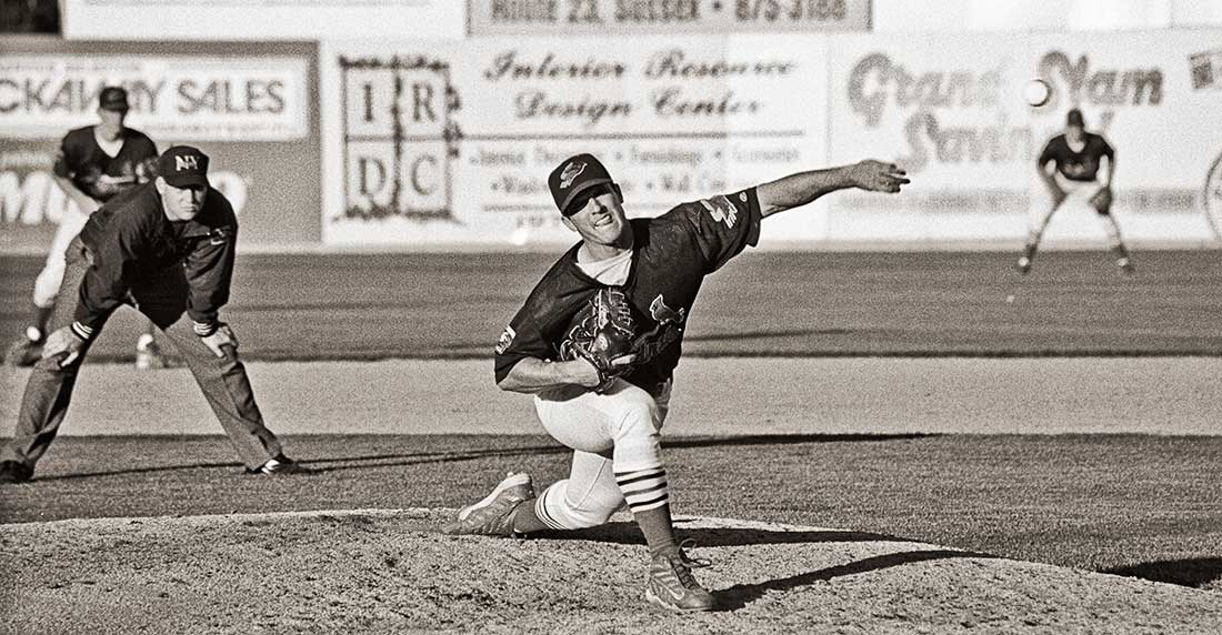 Baseball pitcher pitching baseball.