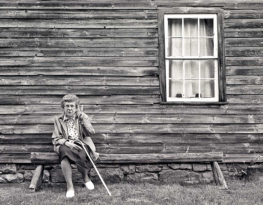Retired woman sitting outside old wooden house