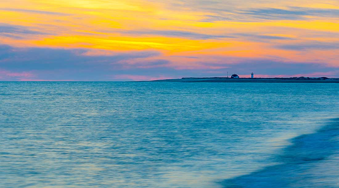 Sunset over lighthouse, Herring Cover Beach, Provincetown, Cape Cod.