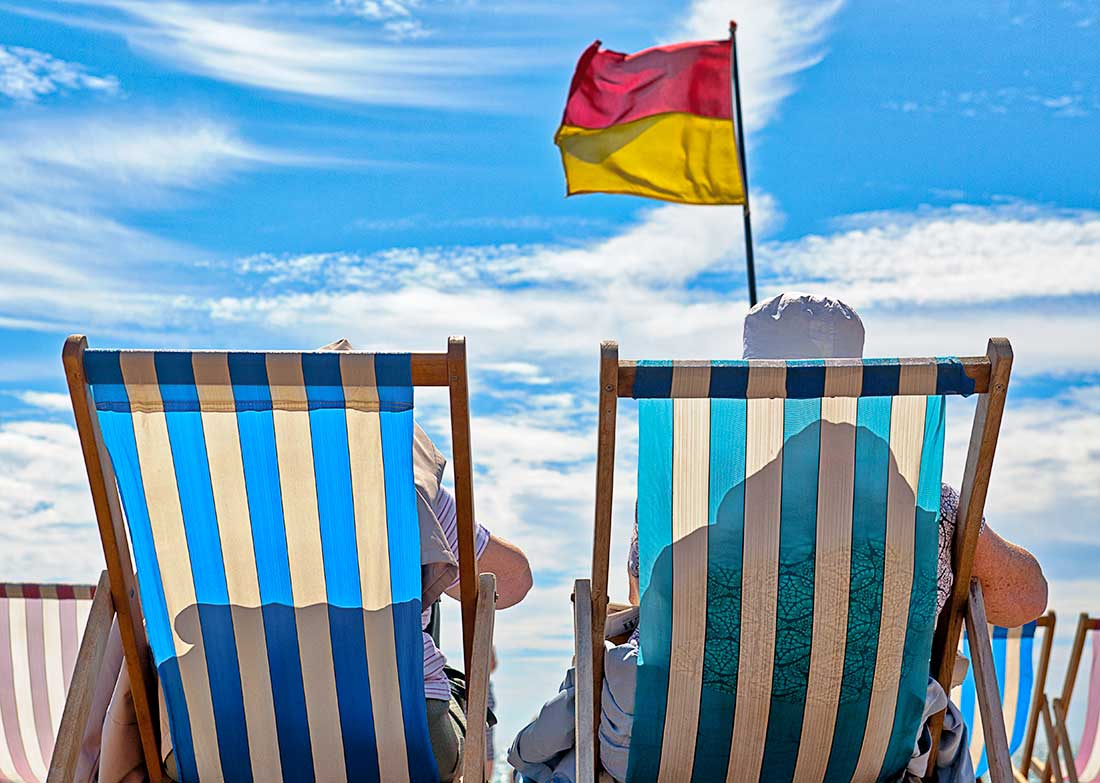 Two people sitting in deck chairs relaxing on the ocean beach in Brighton, England.