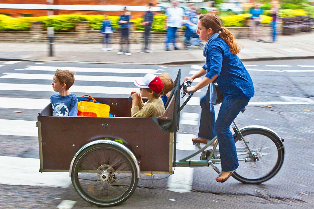 A woman riding a bicycle with a cart attached carrying children.