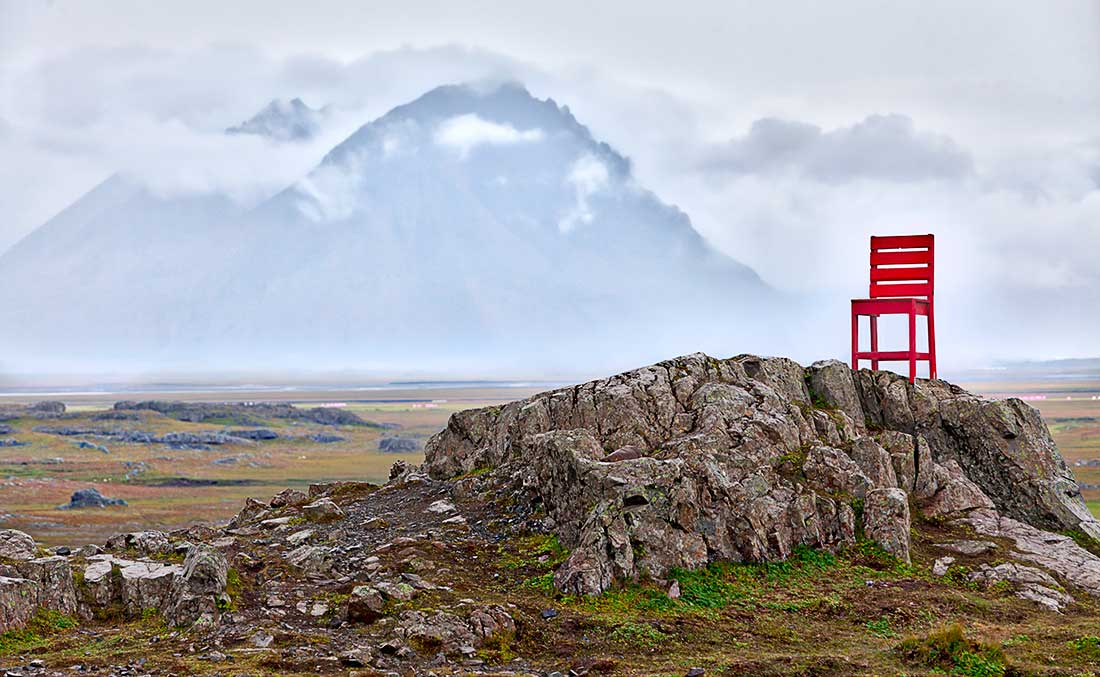 Red chair on rocks in front of mountains and clouds, Iceland.