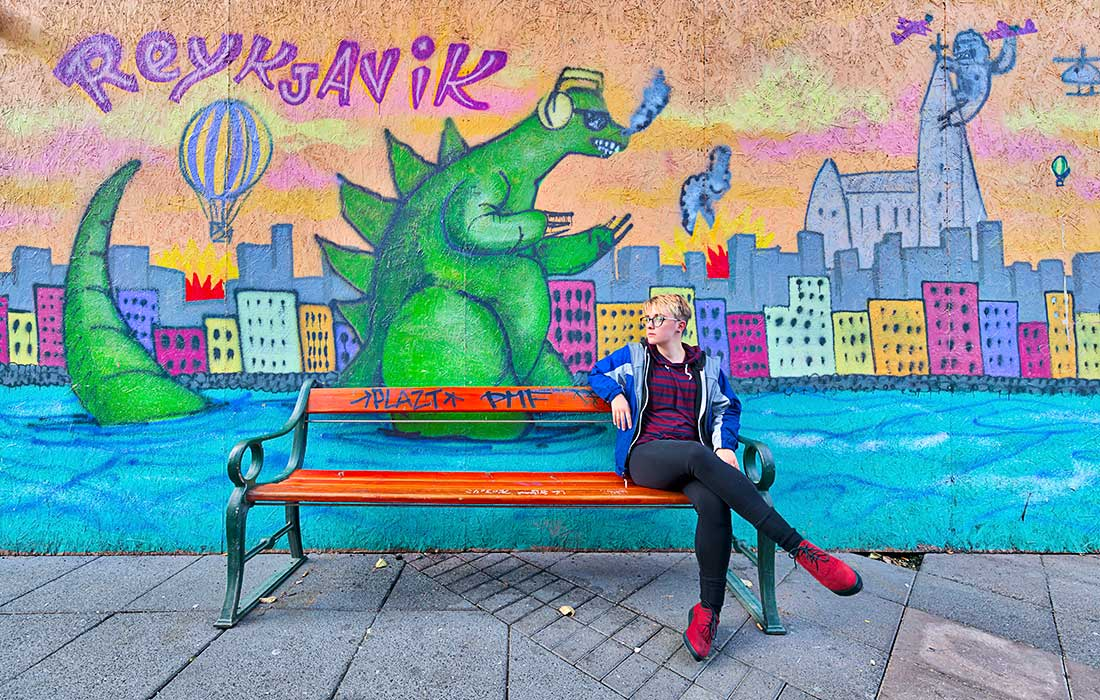 Young woman sits on bench in front of painting with Dinosaur in Reykjavik, Iceland.