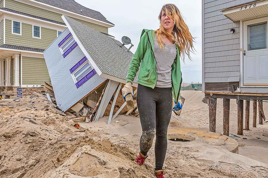 Young woman standing by hurricane damaged home.
