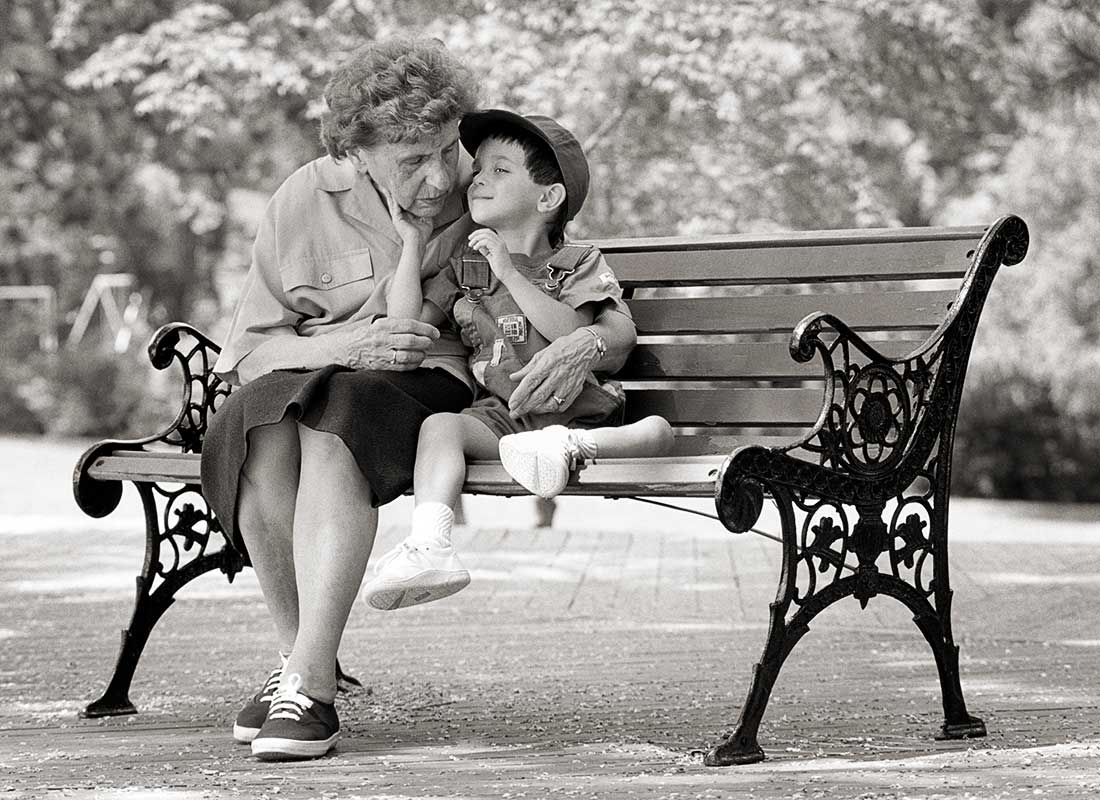 A grandmother hugs her grandson on a park bench.