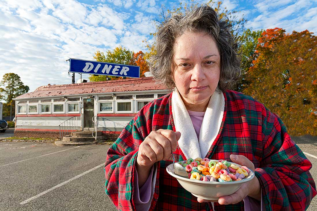 Woman eating cereal in front of a diner.