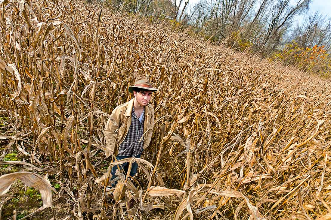 Young man standing in a field of corn.