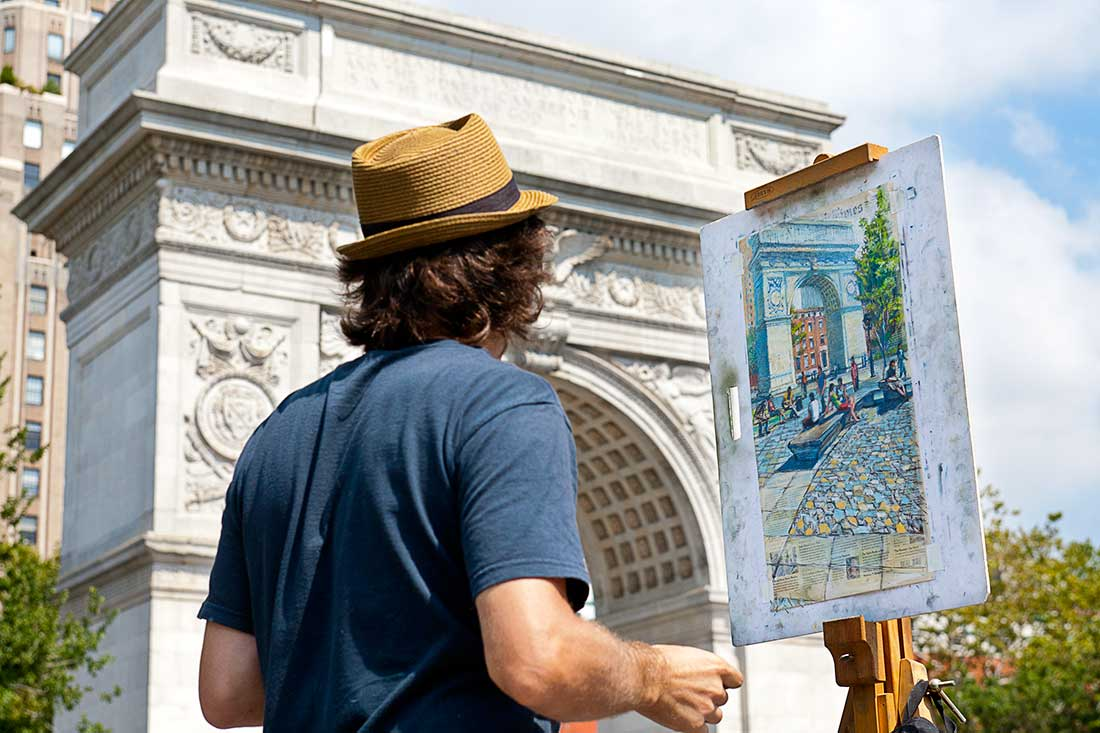 An artist works on his painting in Washington Square Park in Manhattan, New York City.