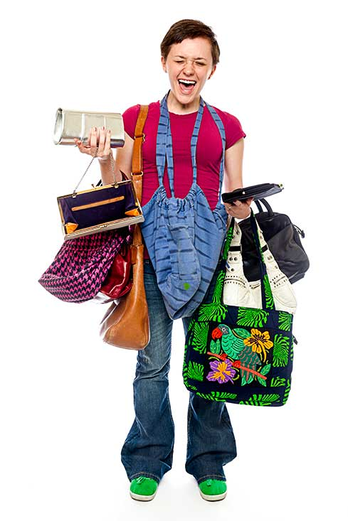 A female teenager poses with a bunch of purses and ladies and women's bags.