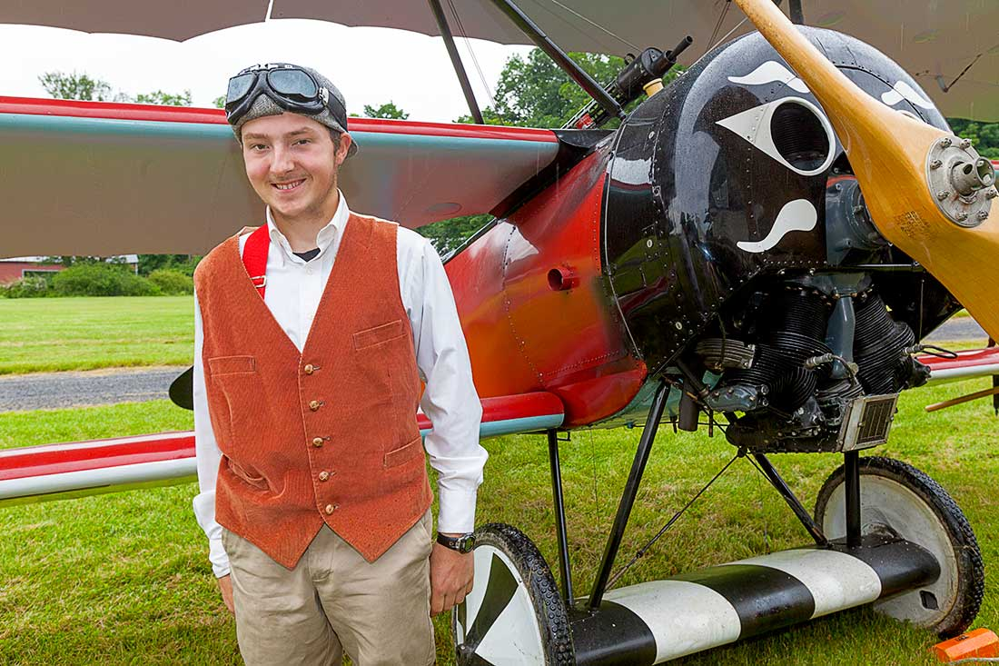 A pilot standing by an antique airplane.