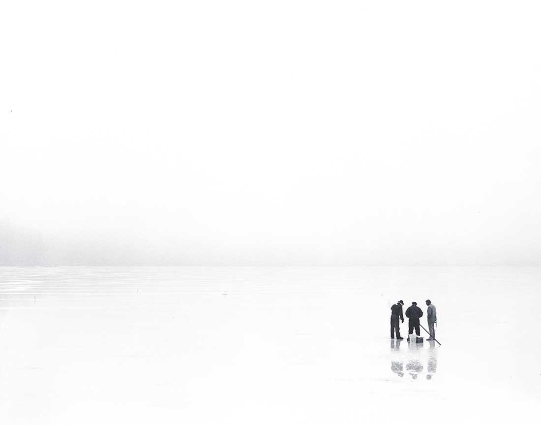 Men Ice Fishing on Frozen Lake