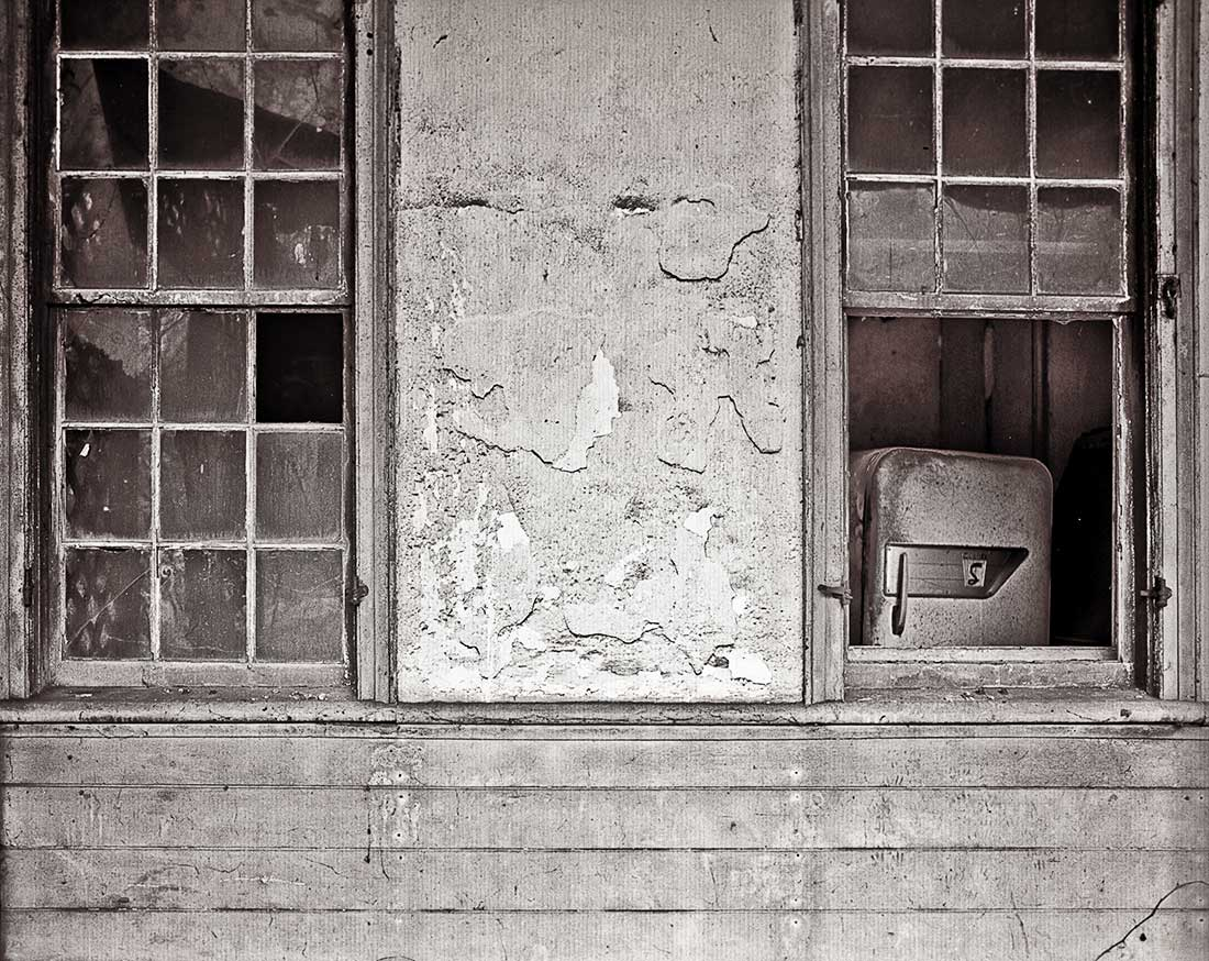 Refrigerator in window of abandoned house.