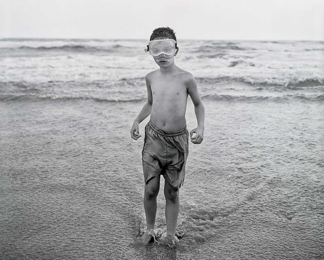 Young boy standing in ocean.