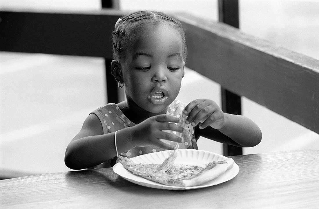 Young African American girl eating a slice of pizza.