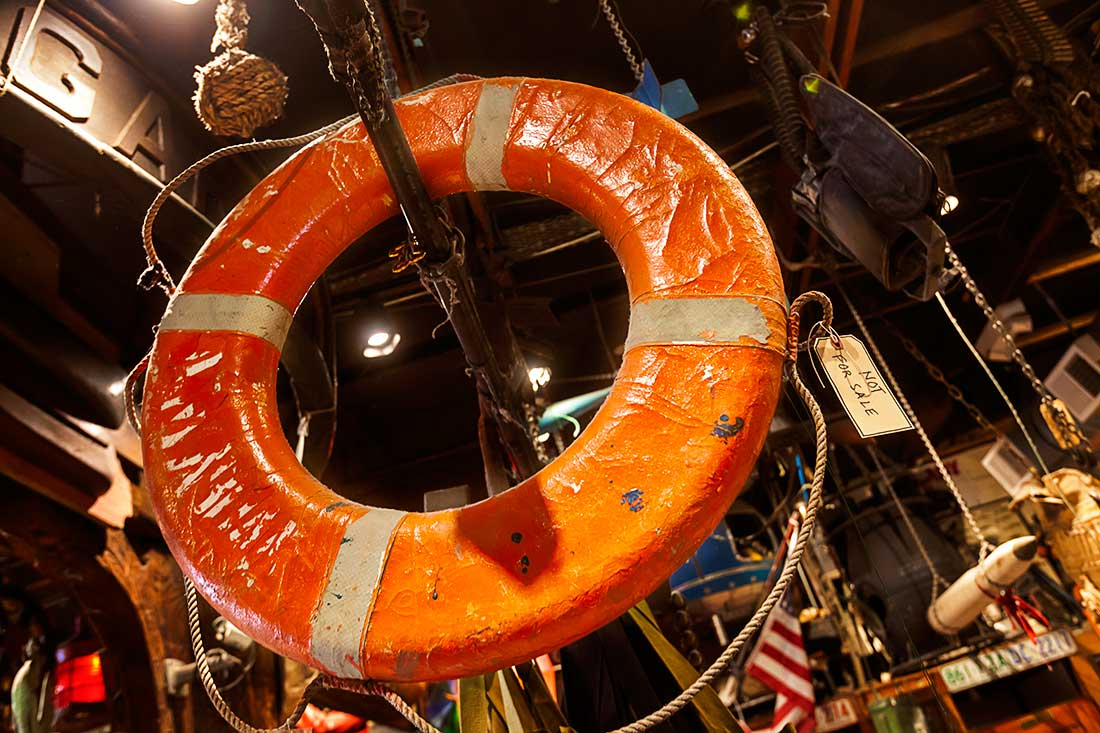 A life Preserver hangs on display in an army navy surplus store.