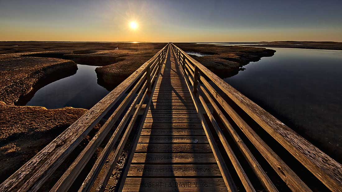 Sunset over the wooden walkway by Grays Beach in Yarmouth, Cape Cod, Massachusetts.
