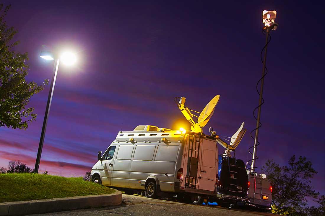 Television news trucks transmitting news during the night.