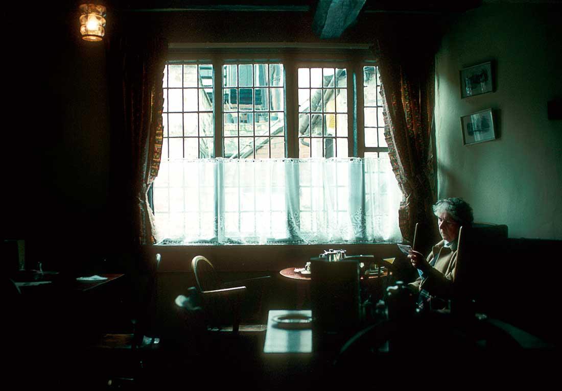 Elderly woman sitting in a pub or restaurant.
