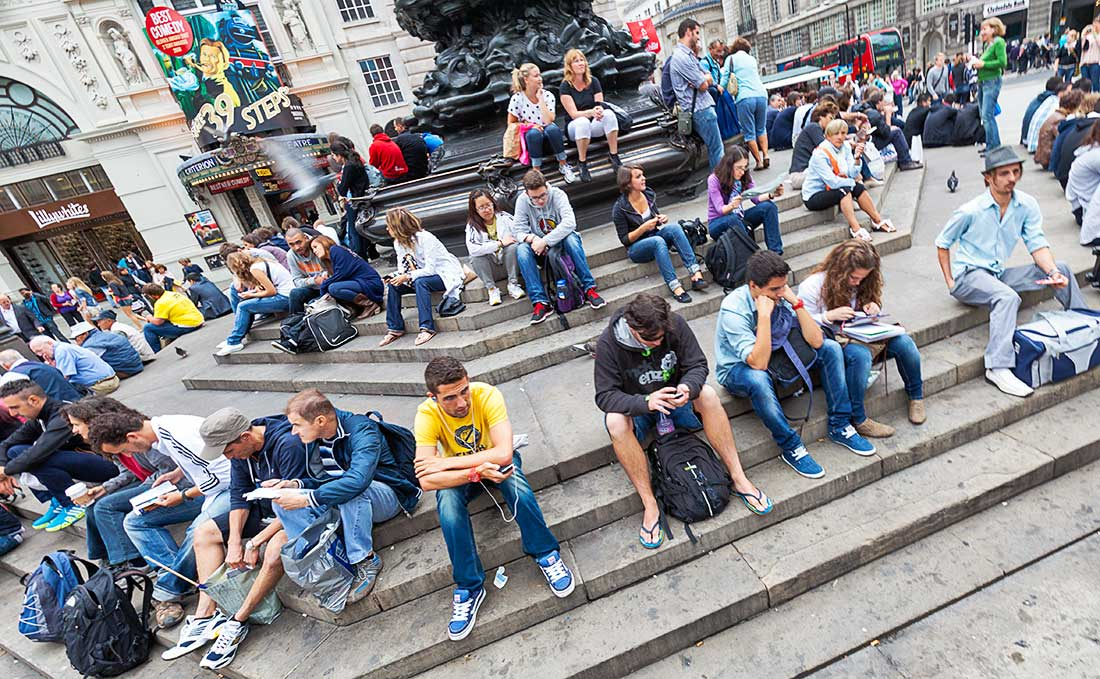 People sitting and resting on the steps of the Piccadilly Circus Monument Sculpture.