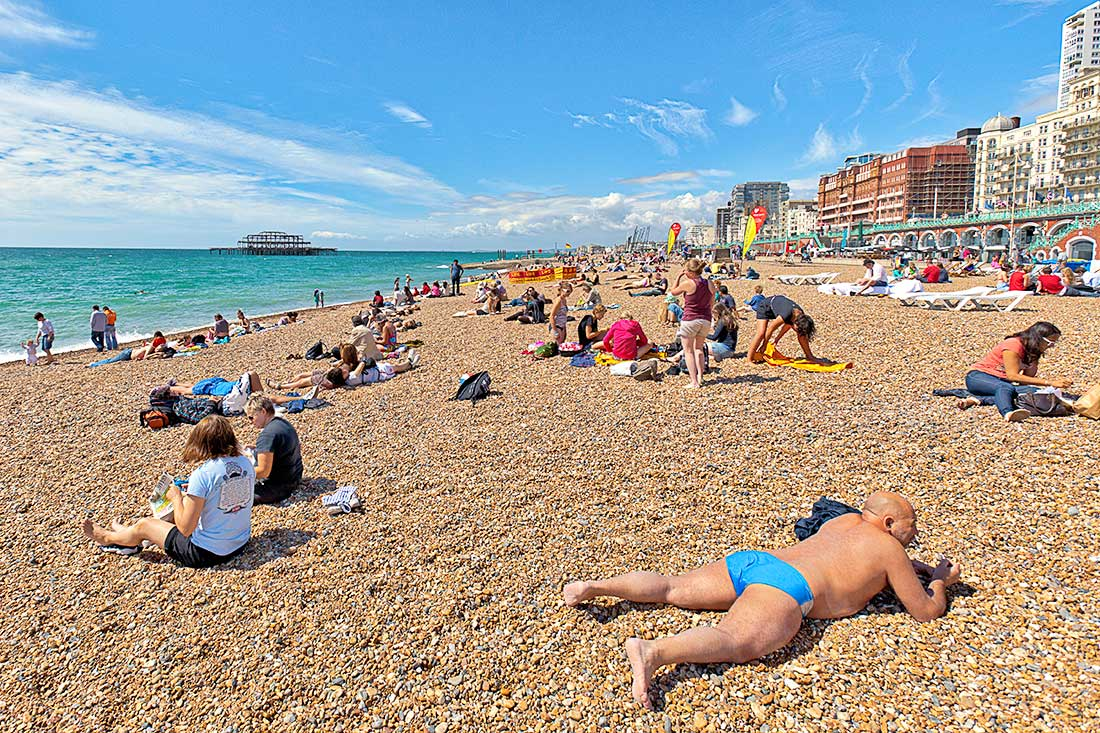Sun bathers and swimmers relaxing on the ocean beach in Brighton, England.