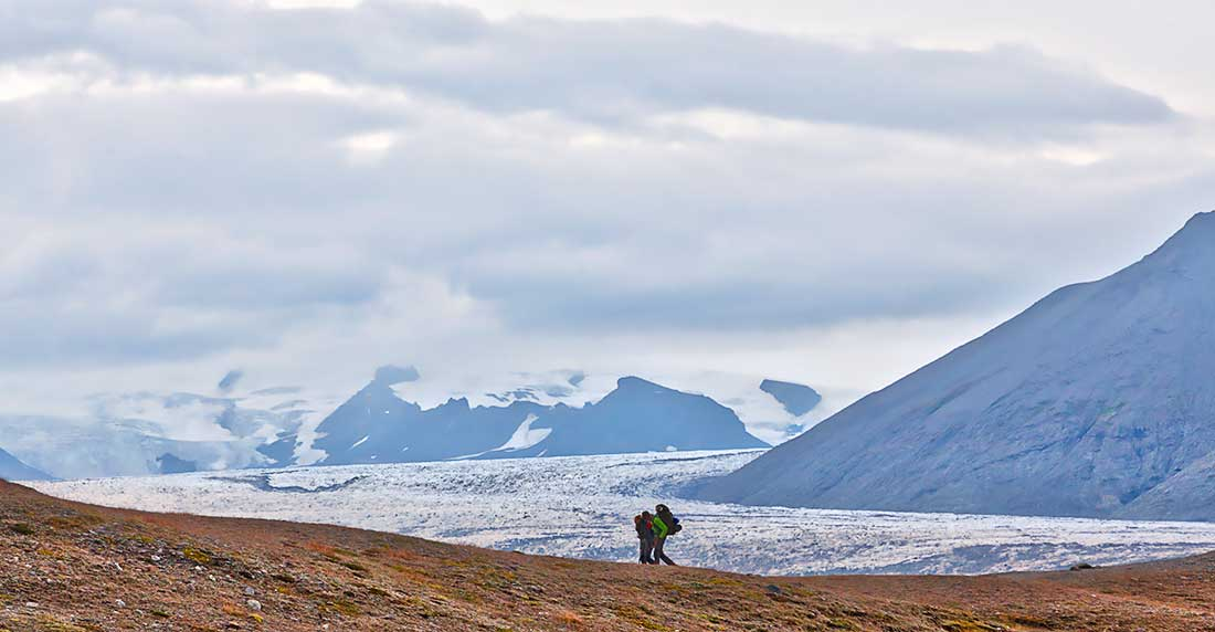 Hikers with mountains, clouds and glaciers around them, Iceland.