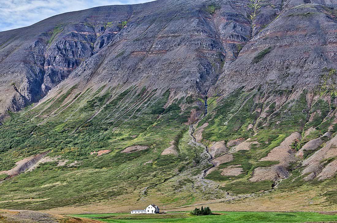 A tiny house sits by a mountain in Iceland.
