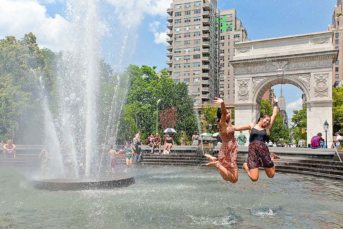 Two women jumping in the fountain in Washington Square Park.