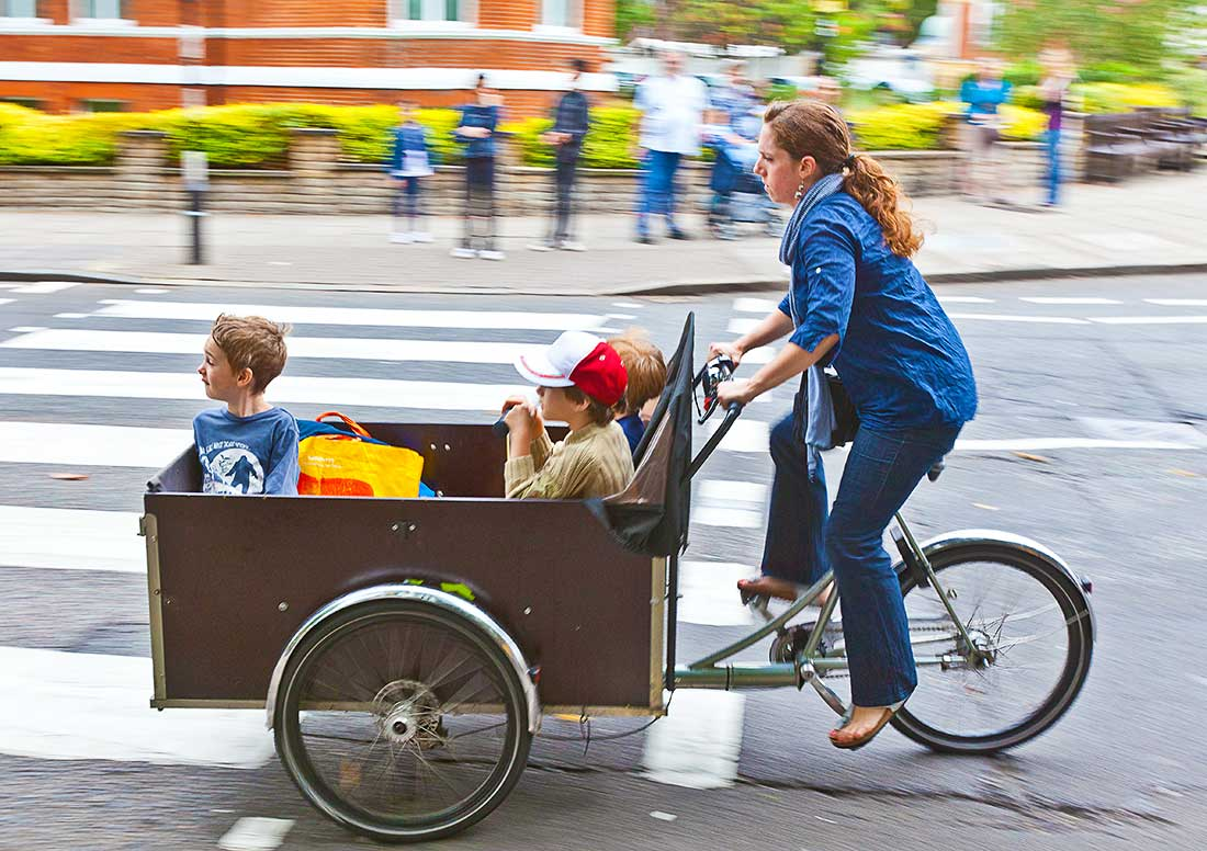 Woman riding bicycle with children.