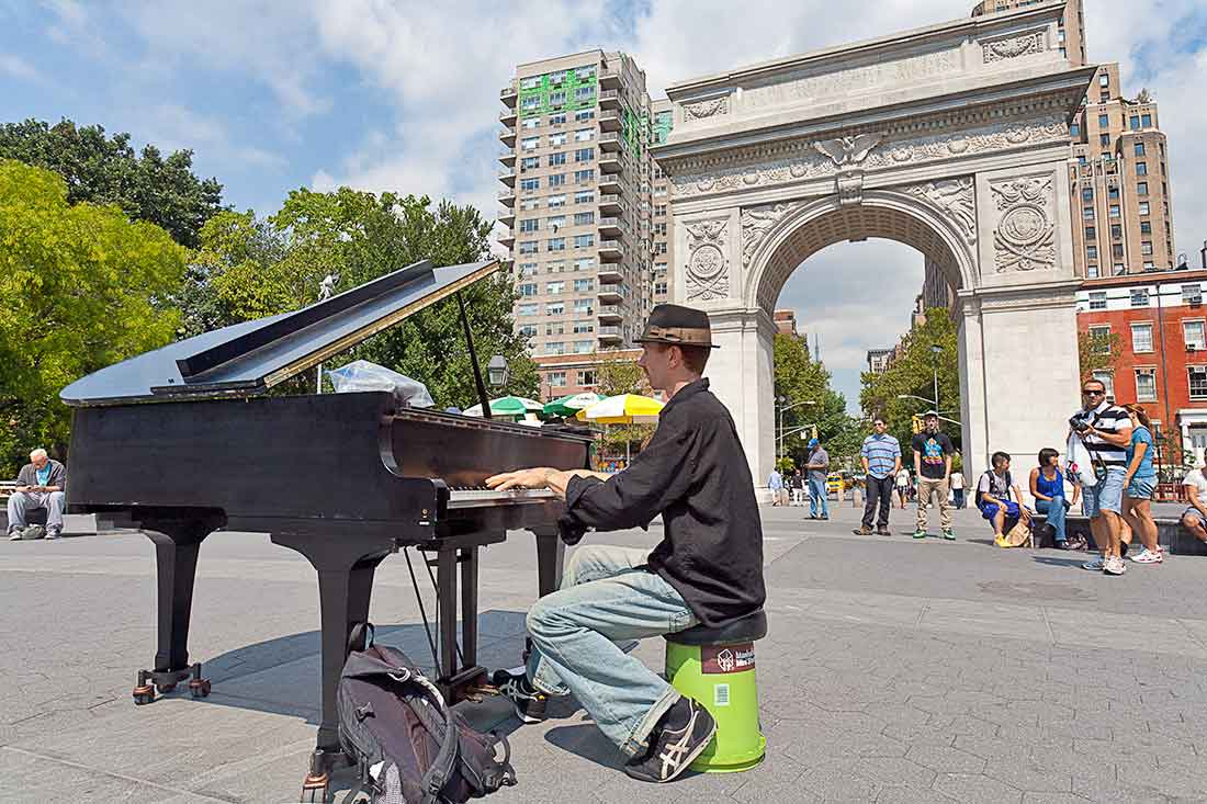 A piano player playing his piano in Washington Square Park in Manhattan, New York City.