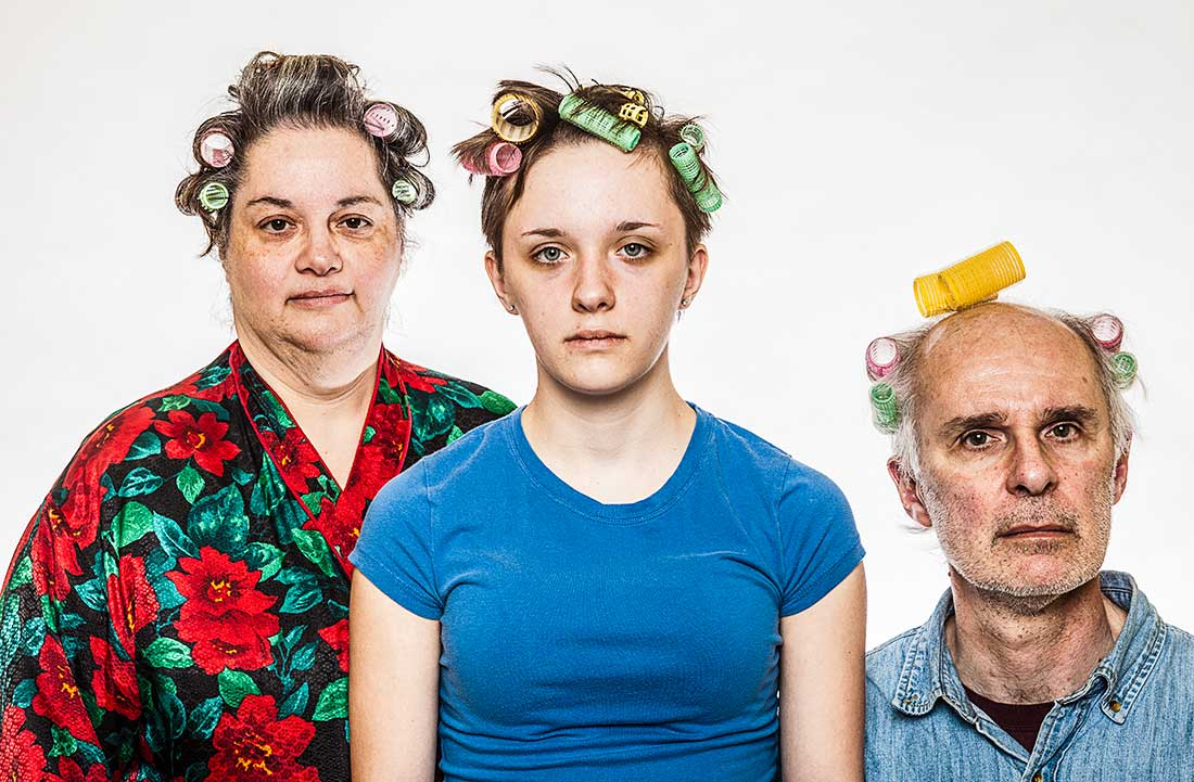A man, a woman and a young woman wearing hair curlers.