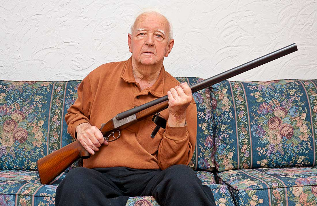 Elderly man holding a shotgun.