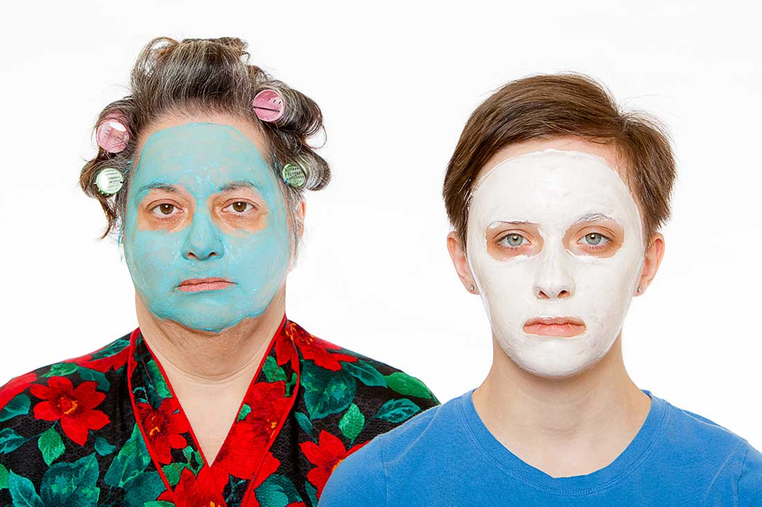A middle aged woman and a female teenager has curlers in their hair and has a beauty face mask on their faces.