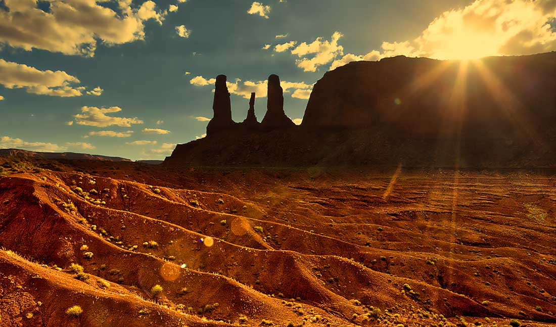 Sunset over the Three Sisters in Monument Valley, Arizona.
